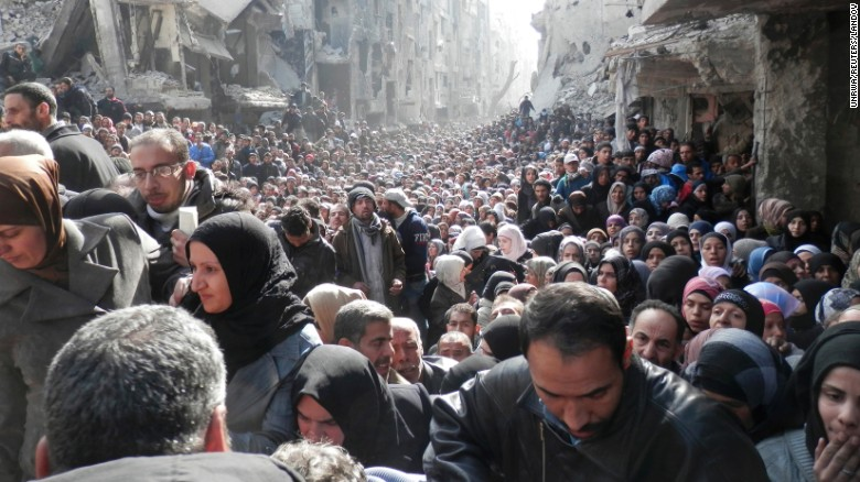 A large crowd of displaced Syrian residents wait for food aid in al-Yarmouk camp